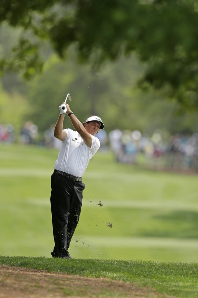 Photo - Phil Mickelson watches his approach shot on the fourth hole during the first round of the Wells Fargo Championship golf tournament in Charlotte, N.C., Thursday, May 1, 2014. (AP Photo/Chuck Burton)