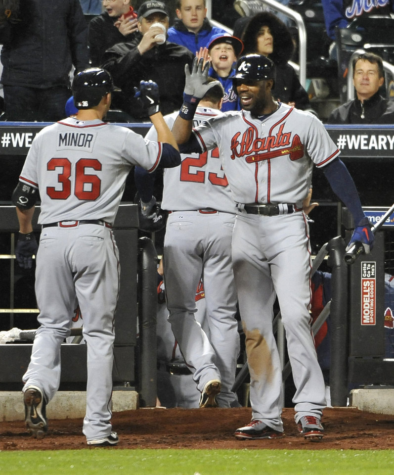 Atlanta Braves' Jason Heyward, right, greets teammate Mike Minor at the dugout after Minor hit a two-run home run off New York Mets starting pitcher Dillon Gee in the fifth inning of the second baseball game at Citi Field, Saturday, May 25, 2013, in New York. (AP Photo/Kathy Kmonicek)