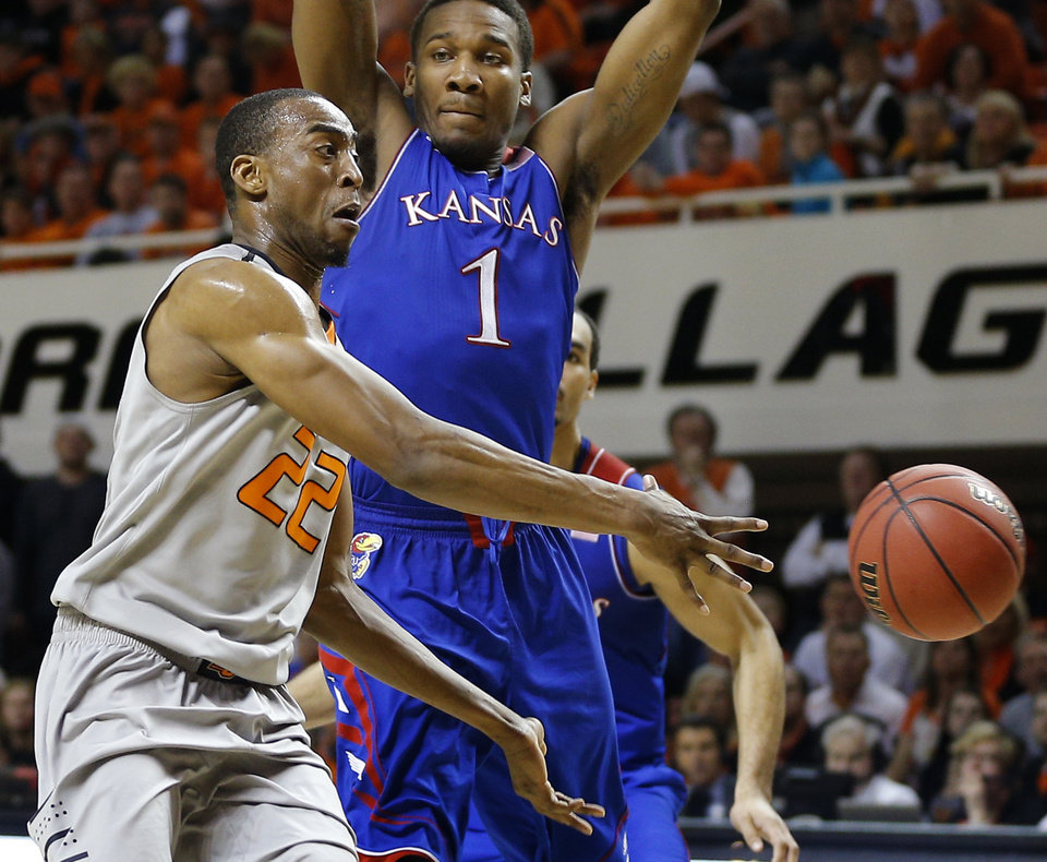Photo - Oklahoma State's Markel Brown (22) passes the ball past Kansas' Wayne Selden, Jr. (1) during an NCAA college basketball game between Oklahoma State University (OSU) and the University of Kansas at Gallagher-Iba Arena in Stillwater, Okla., Saturday, March 1, 2014. Oklahoma State won 72-65. Photo by Bryan Terry, The Oklahoman