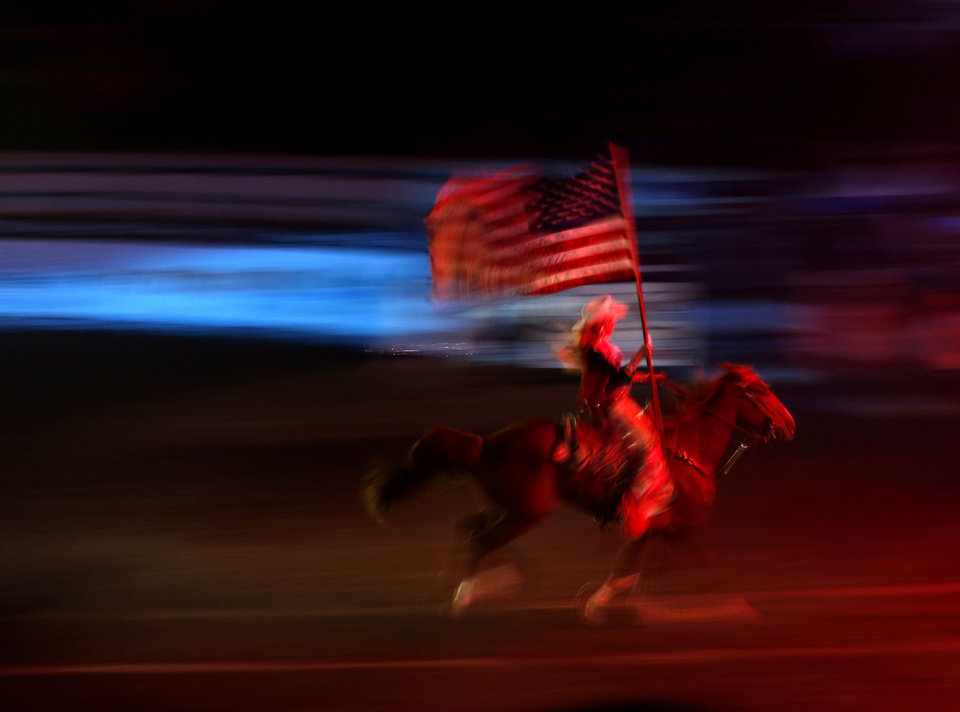 A rider carries the American flag before the start of the National Circuit Finals Rodeo at the State Fair Arena, Saturday, April 6, 2013. Photo by Bryan Terry, The Oklahoman