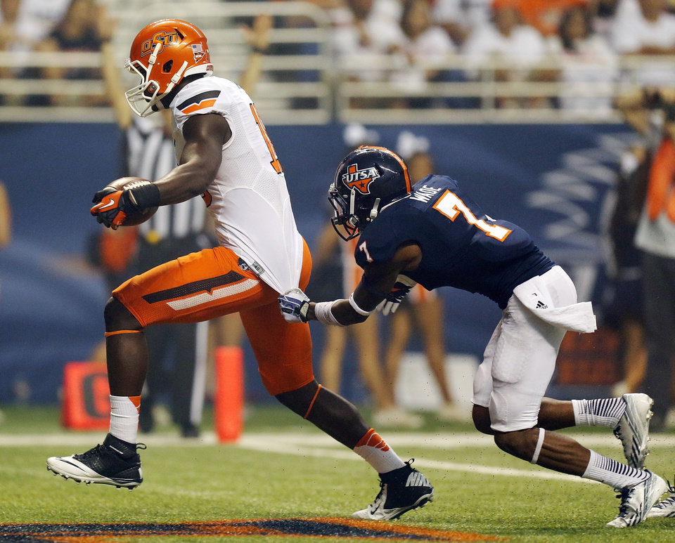 Photo - OSU's Blake Jackson (18) scores a touchdown as UTSA's Triston Wade (7) defends in the third quarter during a college football game between the University of Texas at San Antonio Roadrunners (UTSA) and the Oklahoma State University Cowboys (OSU) at the Alamodome in San Antonio, Saturday, Sept. 7, 2013. OSU won, 56-35. Photo by Nate Billings, The Oklahoman