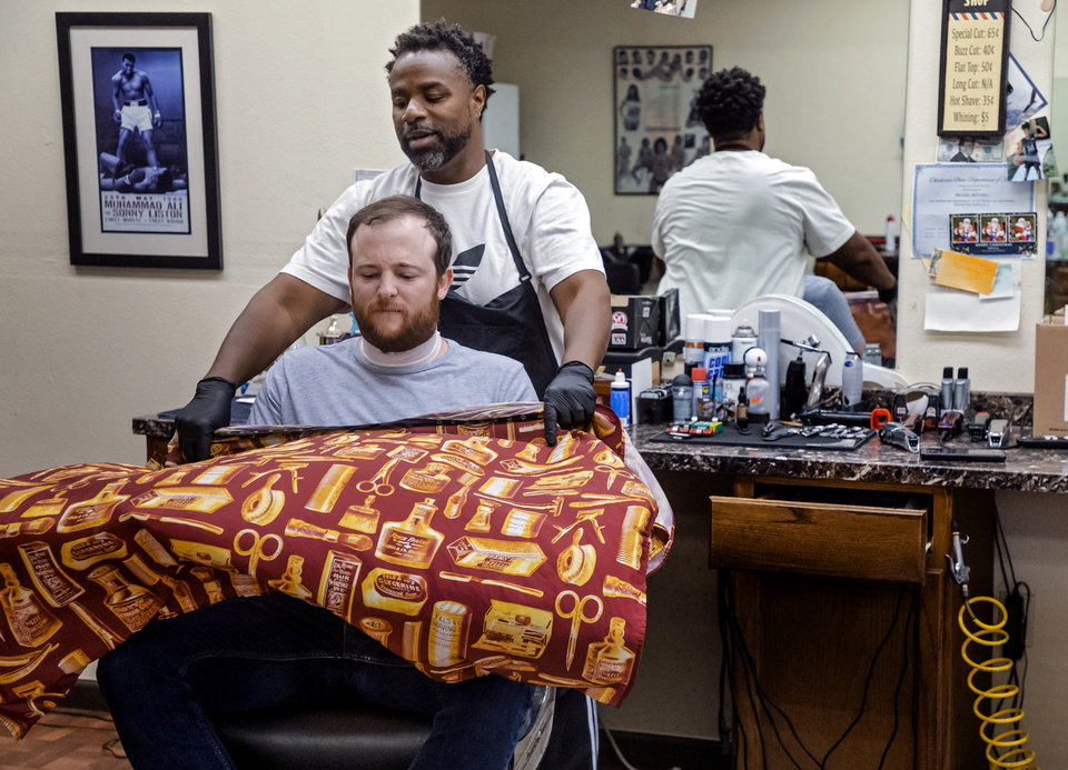 Photo - The Oklahoma's David Dishman prepares to get a haircut and beard trim by Michael Mitchell at Versatile Styles Barber Shop located at 9132 S. Walker Ave. on Tuesday, May 5, 2020, in Oklahoma City, Okla. . [Chris Landsberger/The Oklahoman]