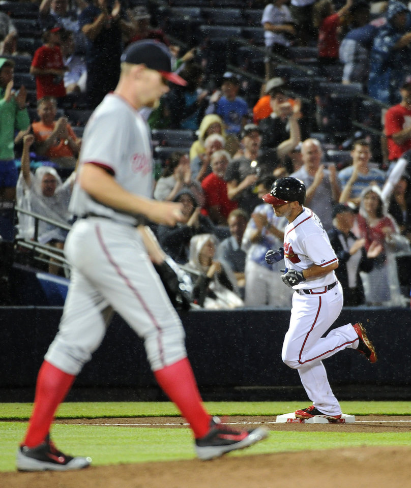 Photo - Atlanta Braves' Tommy La Stella, right, rounds third base behind Washington Nationals pitcher Stephen Strasburg after a solo home run during the fifth inning of a baseball game Friday, Aug. 8, 2014, in Atlanta. (AP Photo/David Tulis)