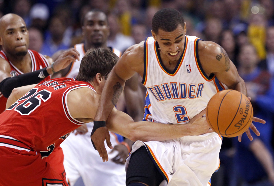 Photo - Oklahoma City's Thabo Sefolosha is fouled by Chicago's Kyle Korver  during the NBA season opener basketball game between the Oklahoma City Thunder and the Chicago Bulls in the Oklahoma City Arena on Wednesday, Oct. 27, 2010. Photo by Sarah Phipps, The Oklahoman