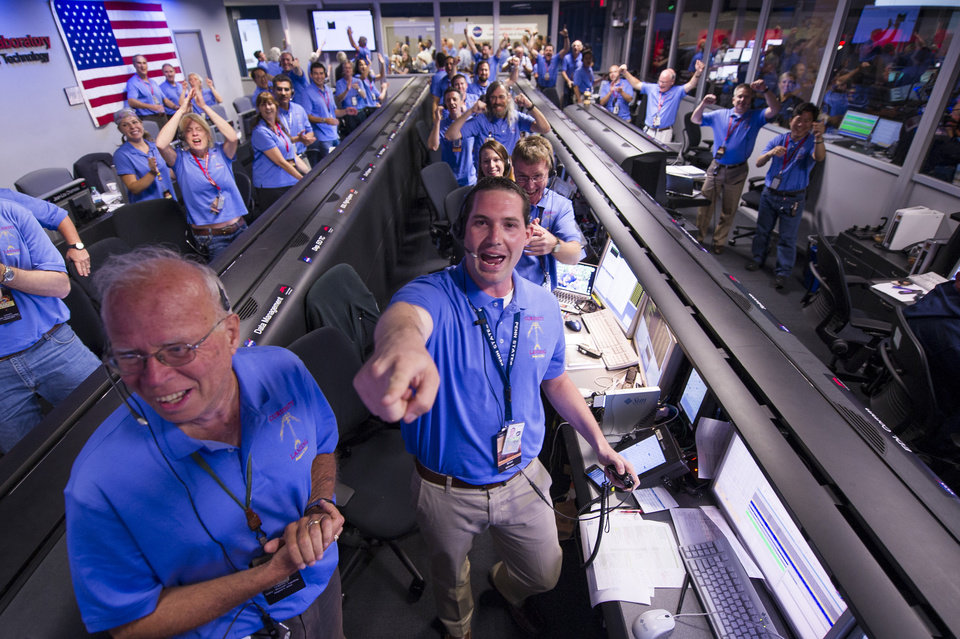 In a photo provided by NASA, the Mars Science Laboratory team in the MSL Mission Support Area reacts after learning the the Curiosity rover has landed safely on Mars and images start coming in at the Jet Propulsion Laboratory on Mars, Sunday, Aug. 5, 2012 in Pasadena, Calif. The MSL Rover named Curiosity was designed to assess whether Mars ever had an environment able to support small life forms called microbes. Photo Credit: (AP Photo/NASA/Bill Ingalls)