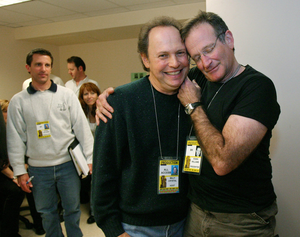 "Photo - FILE - In this Feb. 28, 2004 file photo, Oscar host Billy Crystal, center, and presenter Robin Williams, right, joke around after a writers' meeting for the 76th annual Academy Awards in Los Angeles. Crystal will honor Williams as part of the traditional ""In Memoriam"" segment at the Emmy Awards for industry members who died during the past year. Williams was found dead by suicide in his Northern California home Aug. 11. (AP Photo/Kevork Djansezian, File)"