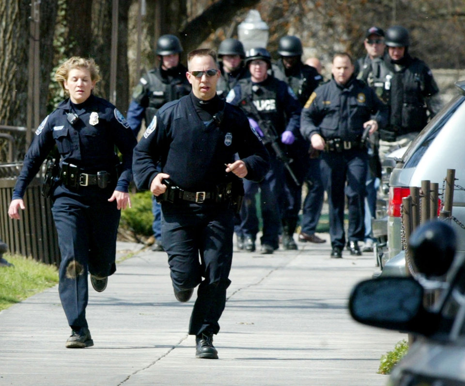 Photo -   FILE - In a Monday, April 16, 2007 file photo, Blacksburg police officers run from Norris Hall on the Virginia Tech campus in Blacksburg, Va. as multiple shootings occur at the engineering building . A gunman opened fire in a Virginia Tech dorm and then, two hours later, in a classroom across campus, killing at least 30 people. Virginia's colleges and universities have quietly investigated hundreds of students, employees and others in recent years to prevent a repeat of the Virginia Tech massacre of 2007, when a student gunman left a series of increasingly disturbing warning signs before killing 32 people and himself. (AP Photo/The Roanoke Times, Matt Gentry, File) MANDATORY CREDIT
