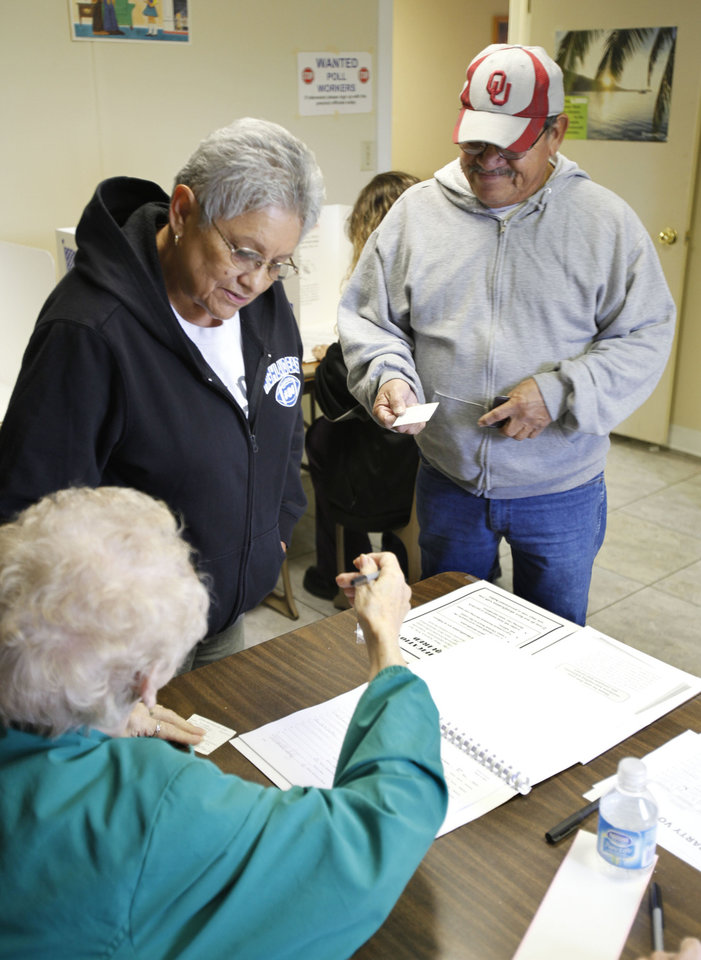 Photo - Genevieve and Leno Soliz sign in to vote at precinct 497 at 1140 SW 29th in Oklahoma City, OK, Tuesday, Nov. 2, 2010. The 497th precinct is one of the smallest in the metro area and typically will receive 20 to 40 voters for the entire day. But by two o'clock more than 100 had already cast votes. By Paul Hellstern, The Oklahoman