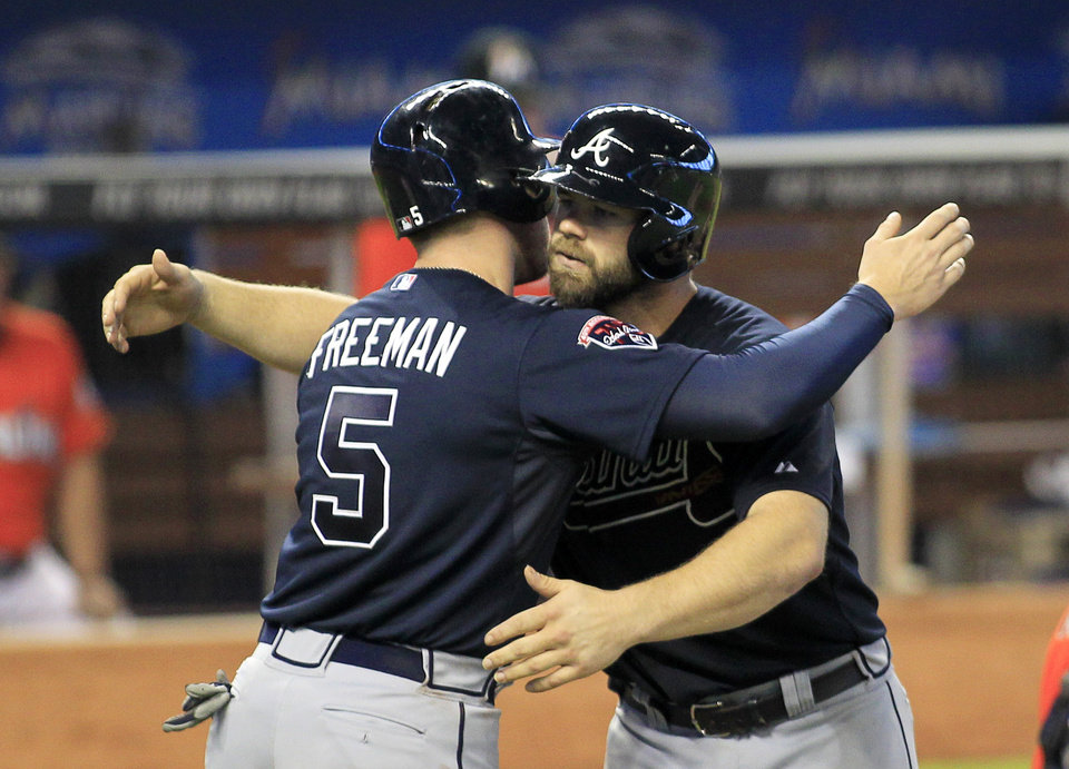 Photo - Atlanta Braves catcher Evan Gattis, right, celebrates with teammate Freddie Freeman after they scored on Gattis' game-winning two-run home run in the ninth inning of a baseball game against the Miami Marlins in Miami, Sunday, June 1, 2014. The Braves completed a three-game sweep of the Marlins with a 4-2 win. (AP Photo/Joe Skipper)