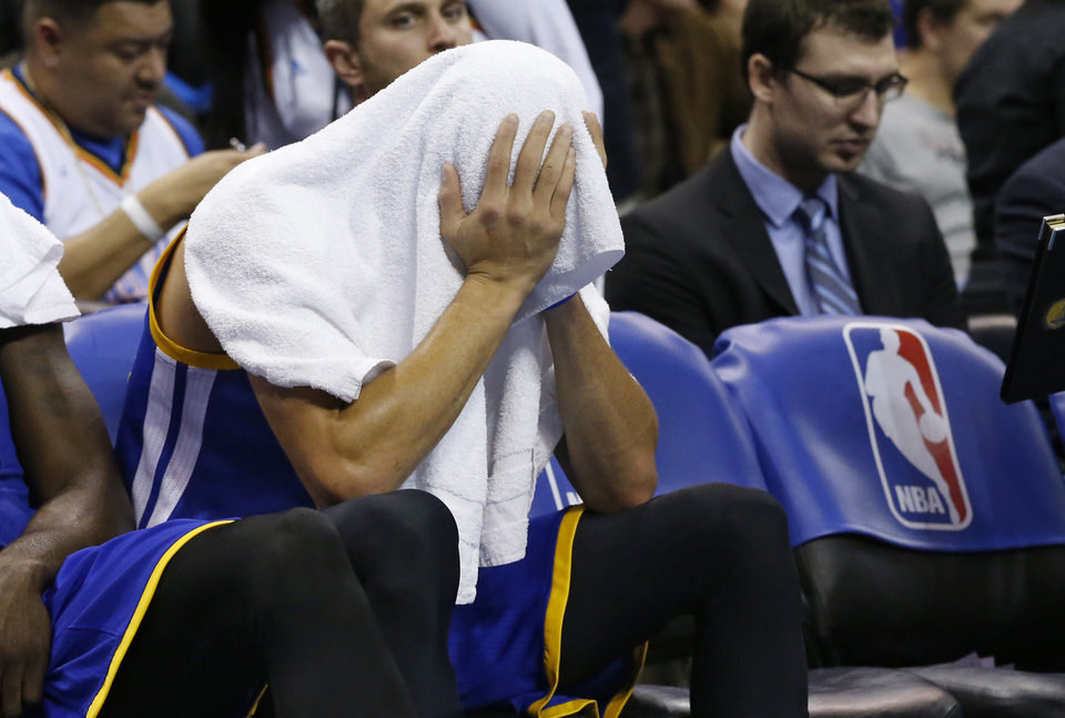 Photo - Golden State Warriors guard Stephen Curry sits on the bench with a towel over his head late in the fourth quarter of an NBA basketball game against the Oklahoma City Thunder in Oklahoma City, Friday, Jan. 16, 2015. Oklahoma City won 127-115. (AP Photo/Sue Ogrocki)