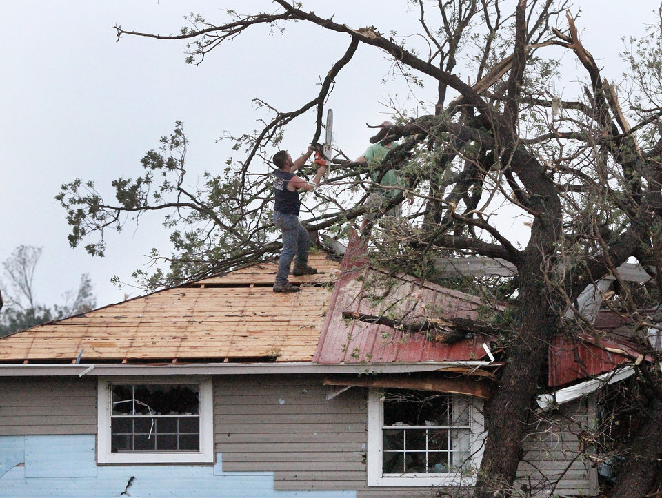 Photo - A man uses a chain saw to cut branches from a fallen tree on the roof of this home on US 177 north of I-40.  A tornado caused extensive damage along I-40 at the junction with  US 177 on the west side of Shawnee Sunday evening,  May 19,  2013.  Photo  by Jim Beckel, The Oklahoman.