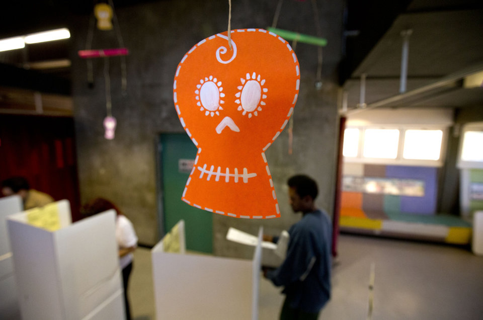 A man heads to vote in a booth as decorations for the traditional Mexican Day of the Dead celebration hang overhead at a Sherman Heights cultural center and polling station Tuesday, Nov. 6, 2012, in San Diego. (AP Photo/Gregory Bull)