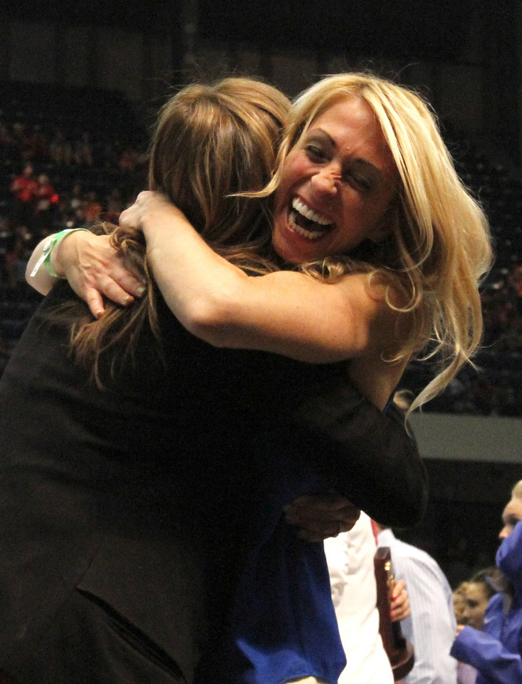 Photo - Oklahoma's coach KJ Kindler, left, and Florida coach Rhonda Faehn, right, celebrate after being crowned co-champions during the NCAA college women's gymnastics championships on Saturday, April 19, 2014, in Birmingham, Ala. (AP Photo/Butch Dill)