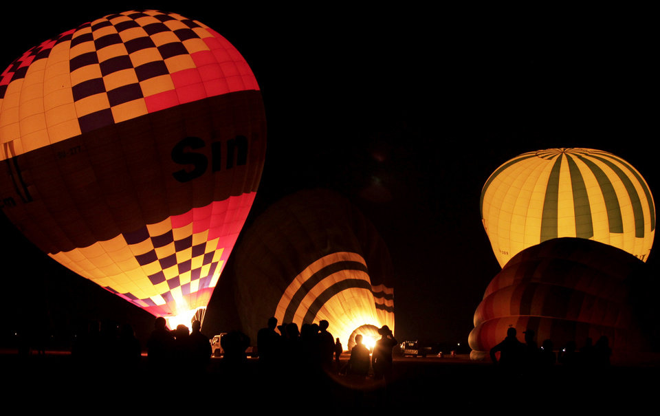 Photo - FILE - In this Friday, Nov. 23, 2012 file photo, tourists wait their turns to ascend in hot air balloons before sunrise in Luxor, Egypt. A hot air balloon flying over Egypt's ancient city of Luxor caught fire and crashed into a sugar cane field outside al-Dhabaa village, just west of the city of Luxor,  Egypt, Tuesday, Feb. 26, 2013, killing at least 18 foreign tourists, a security official said. Hot air ballooning, usually at sunrise over the famed Karnak and Luxor temples as well as the Valley of the Kings, is a popular pastime for tourists visiting Luxor. (AP Photo/Nariman El-Mofty, File)