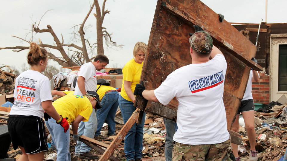 Photo - Volunteers from two different groups, Mormon Helping Hands and Operation Blessing International, help a Moore resident after a tornado destroyed her home May 20. Photo provided by Mormonnewsroom.org.