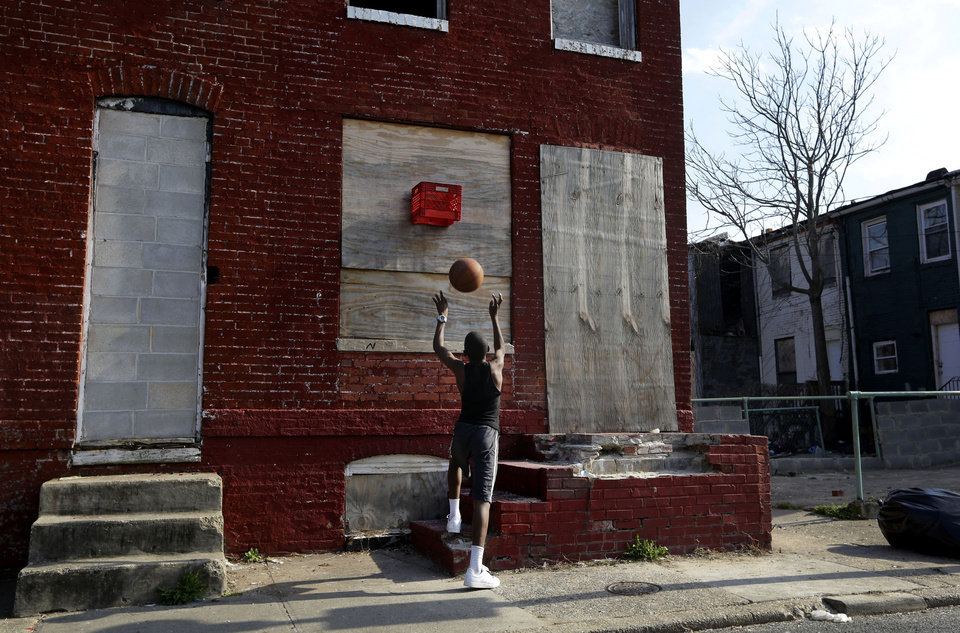 Photo - In this April 8, 2013 picture, a boy shoots a basketball into a makeshift basket made from a milk crate and attached to a vacant row house in Baltimore. The U.S. Census Bureau estimates that 20 percent of American children are impoverished. An estimated 16,000 buildings are vacant or abandoned in Baltimore. (AP Photo/Patrick Semansky)