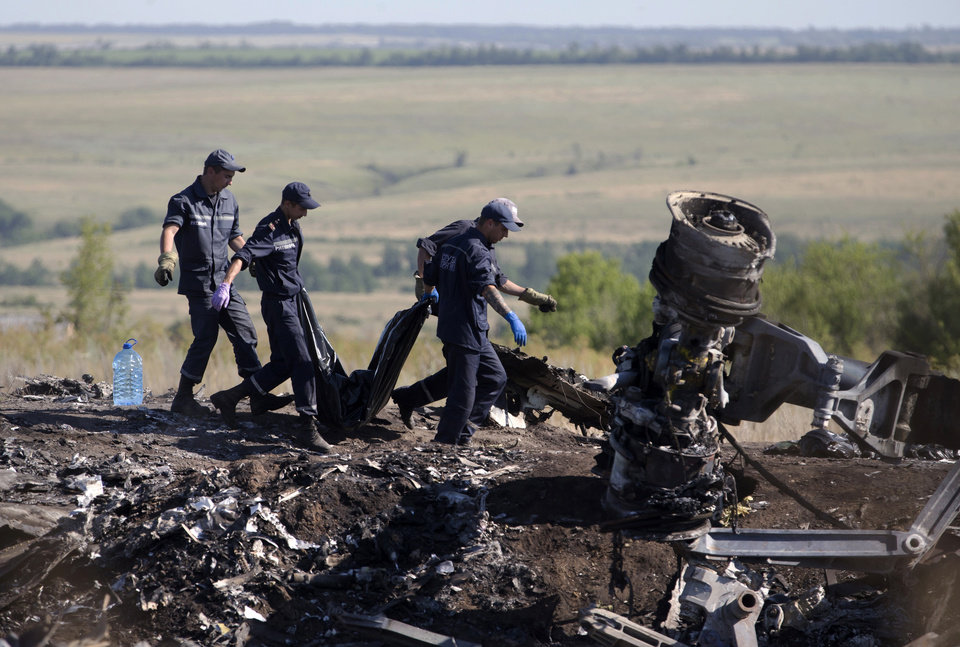 Photo - Ukrainian Emergency workers carry a victim's body in a plastic bag at the crash site of Malaysia Airlines Flight 17 near the village of Hrabove, Donetsk region, eastern Ukraine Monday, July 21, 2014. Another 21 bodies have been found in the sprawling fields of east Ukraine where Malaysia Airlines Flight 17 was downed last week, killing all 298 people aboard. (AP Photo/Dmitry Lovetsky)