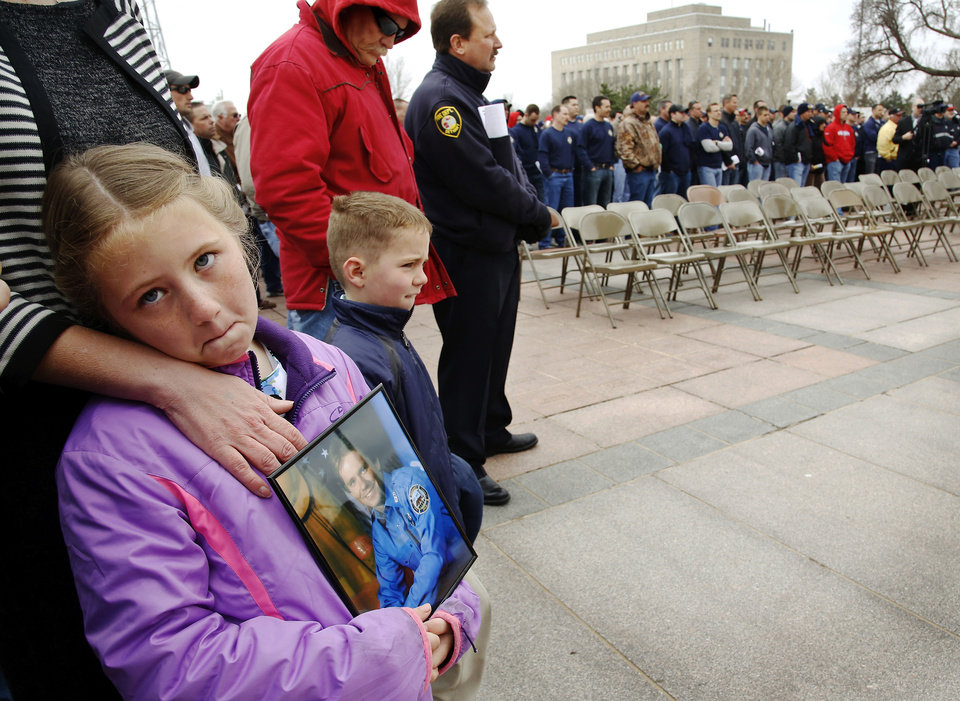 Photo - Cadence Treece, 7, holds a photo of her dad, Lt. Wesley Treece,  a lieutenant with 14 years of service in the Shawnee Fire Department who died of colon cancer  in March  2009.  Treece was 42. Lt. Treece was among hundreds   of firefighters who responded to the scene in Oklahoma City after the Alfred P. Murrah Federal Building was destroyed in a bombing on April 19, 1995. Cadence attended the rally with her brother, Richard, right,  and their mother, Richelle (cq). An estimated 400 active and retired firefighters from across Oklahoma rallied on the south plaza of the state Capitol Monday morning, March 18, 2013, before going inside the building to visit with lawmakers and voice their concerns about proposed changes in pension and workers' compensation systems.      Photo by Jim Beckel, The Oklahoman