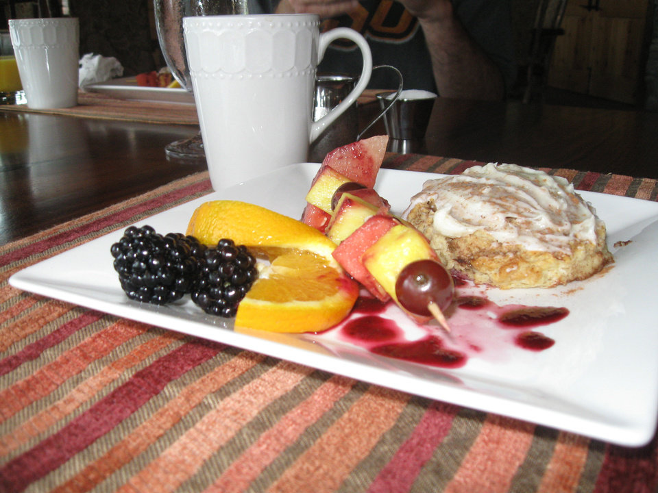 Photo - Stonewater's signature breakfast appetizer features raspberries, oranges, grapes, pineaapple and watermelon and a cinnamon roll. PHOTO BY PAULA BURKES, THE OKLAHOMAN