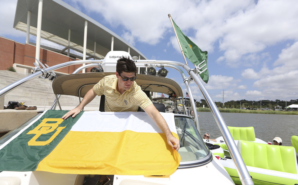 Photo - Ryan Leeper adjusts a flag on his friend's power boat tied off on the Brazos River outside new McLane Stadium before an NCAA college football game between SMU and Baylor, Sunday, Aug. 31, 2014, in Waco, Texas. (AP Photo/LM Otero)