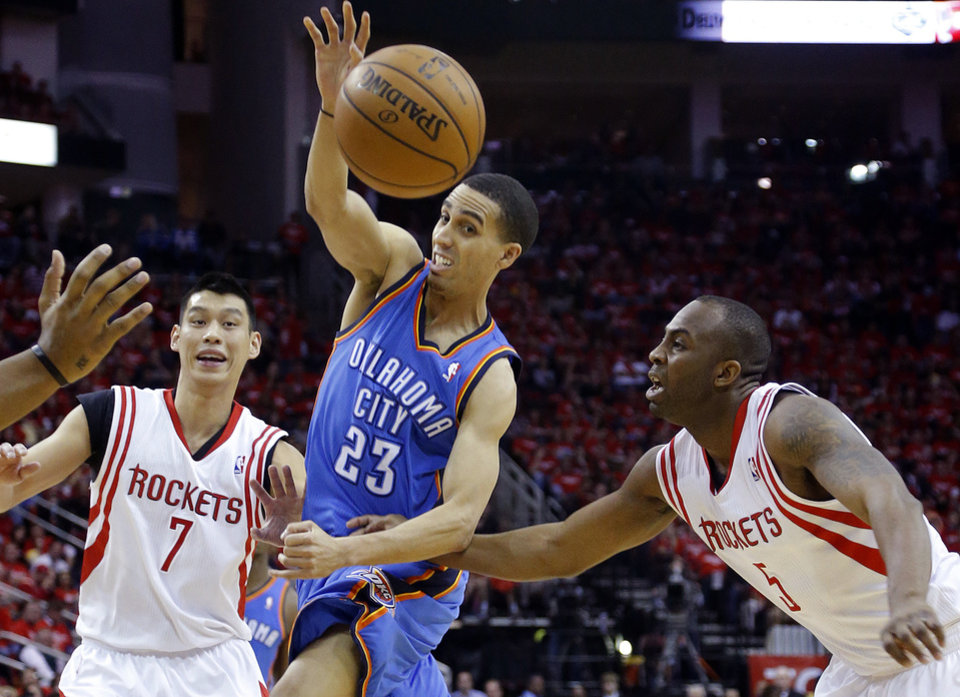 Oklahoma City\'s Kevin Martin (23) passes the ball in between Houston\'s Jeremy Lin (7) and James Anderson (5) during Game 6 in the first round of the NBA playoffs between the Oklahoma City Thunder and the Houston Rockets at the Toyota Center in Houston, Texas, Friday, May 3, 2013. Photo by Bryan Terry, The Oklahoman