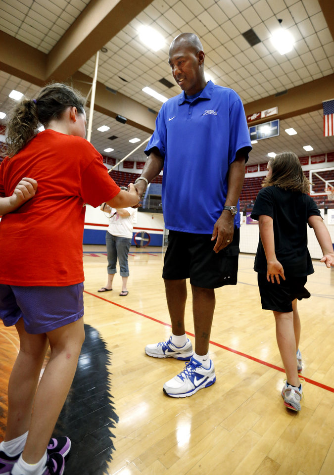 Brooke Smith, Plaza Towers elementary student, ges a handshake from former NBA All-Star Danny Manning as Manning, Otis Birdsong and Michael Ray Richardson host a basketball clinic for tornado victims on Thursday, June 13, 2013 in Moore, Okla.  Photo by Steve Sisney, The Oklahoman