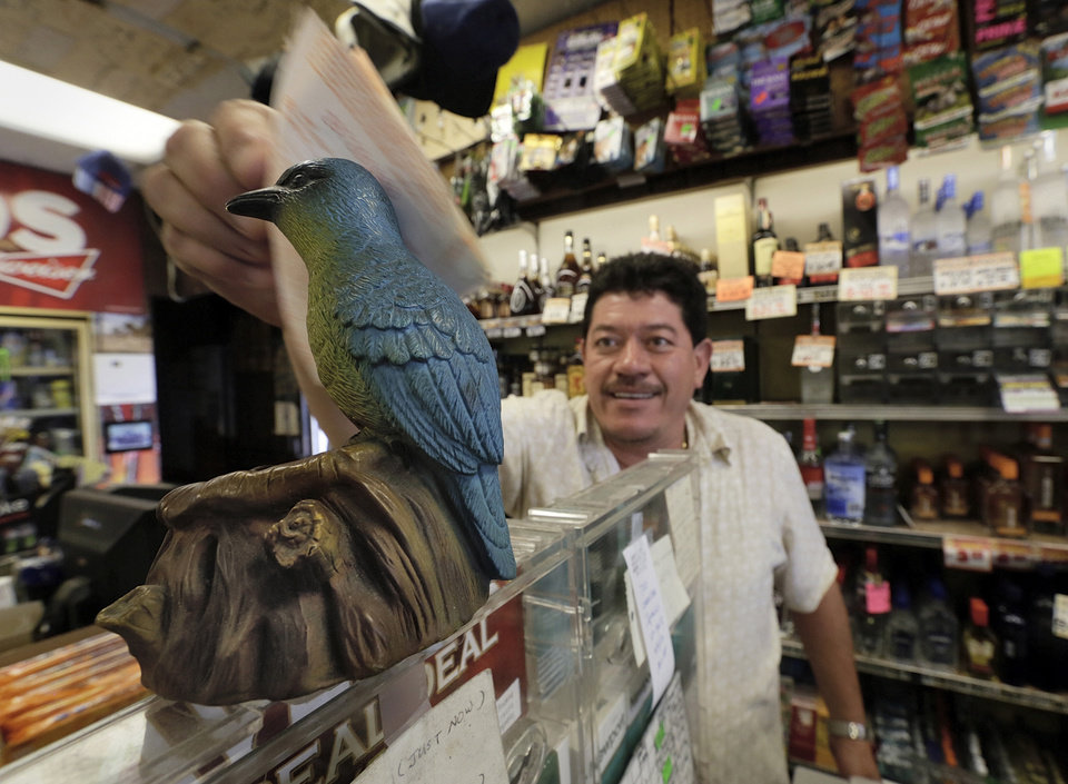 Photo - Ronald Marin rubs his lottery tickets on the wings of a