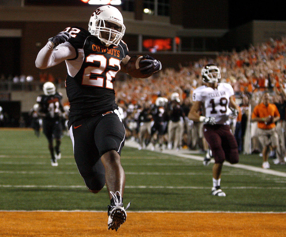 Photo - OSU's James Thomas (22) scores on a fumble recovery for touchdown as A&M's Micheal Lamothe chases him down during the college football game between Texas A&M University (TAMU) and Oklahoma State University (OSU) at Boone Pickens Stadium in Stillwater, Okla., Thursday, Sept. 30, 2010. Photo by Sarah Phipps, The Oklahoman