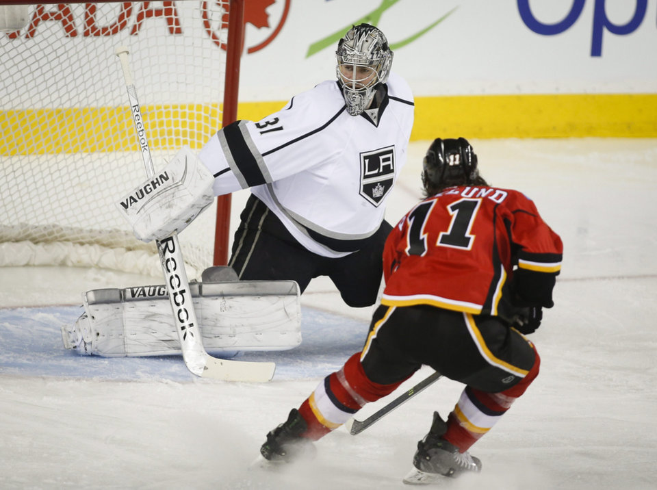 Photo - Los Angeles Kings goalie Martin Jones, left, gets pressured by Calgary Flames' Mikael Backlund, from Sweden, during second period NHL hockey action in Calgary, Alberta, Monday, March 10, 2014. (AP Photo/The Canadian Press, Jeff McIntosh)