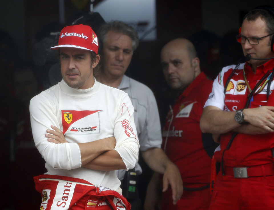 Photo - Ferrari driver Fernando Alonso, left, of Spain waits in his team garage due to a rain-delayed of the qualifying session for Sunday's Malaysian Formula One Grand Prix at Sepang International Circuit in Sepang, Malaysia, Saturday, March 29, 2014. (AP Photo/Peter Lim, Pool)
