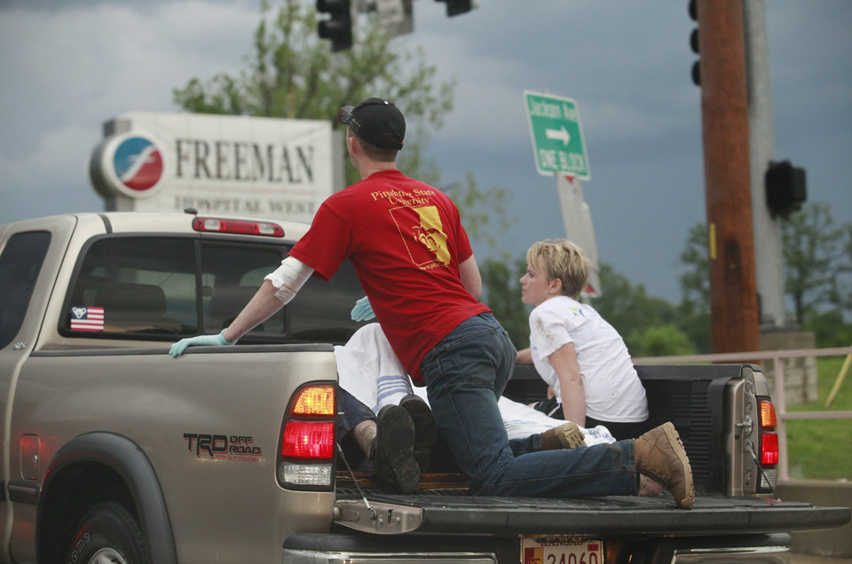Photo - A pickup truck with what looked like two rescue workers and two injured people weaves in and out of traffic to get to Freeman Hospital West in Joplin, Mo. after the town was hit by a tornado on Sunday, May 22, 2011. (AP Photo/The Wichita Eagle, Jaime Green) ORG XMIT: KSWIE103