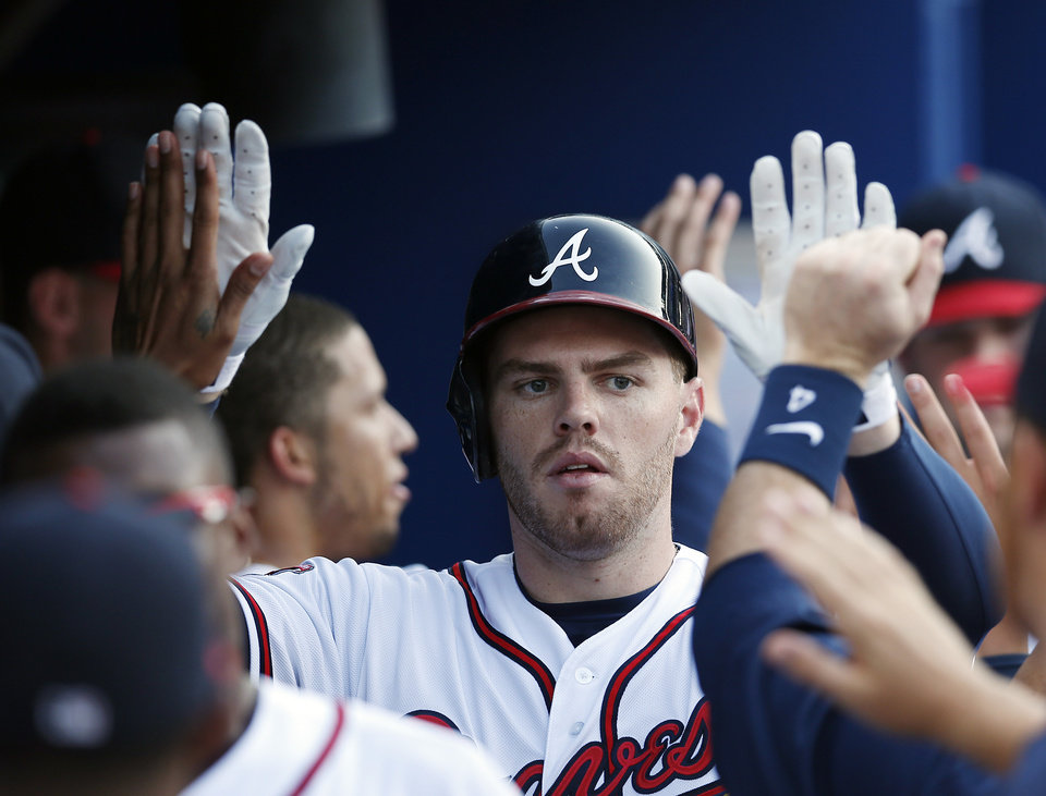 Photo - Atlanta Braves first baseman Freddie Freeman (5) celebrates in the dugout after hitting a three-run home run in the second inning of baseball game against the Miami Marlins  in Atlanta, Wednesday, July 23, 2014. (AP Photo)