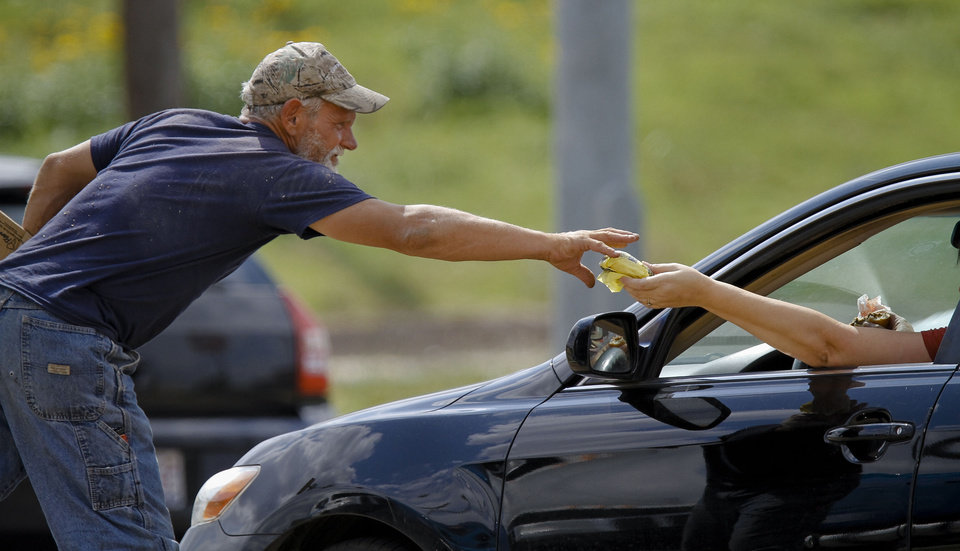 Raymond Hauser, 50, of Joplin, Mo. is handed a hamburger from a motorist as he panhandles the intersection at I-40 and MacArthur Blvd. on Wednesday, Sept. 26, 2012, in Oklahoma City, Okla. Hauser ended up in Oklahoma after being stranded while hitchhiking to California a month ago.  Photo by Chris Landsberger, The Oklahoman