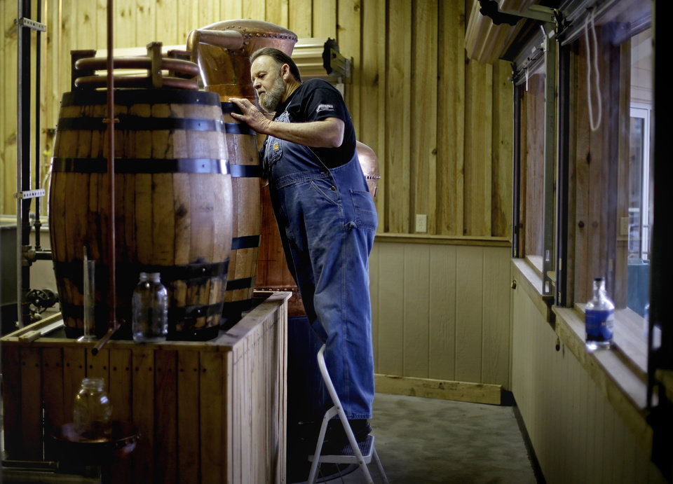 In this Friday, Nov. 16, 2012 photo, distiller Dwight Bearden stands over a condenser barrel while making a batch of genuine corn whisky moonshine in the Dawsonville Moonshine Distillery in Dawsonville, Ga. Distillers are making their first batches of legal liquor in this tiny Georgia town's hall, not far from the mountains and the maroon, orange and gold canopy of trees that once hid bootleggers from the law. (AP Photo/David Goldman)