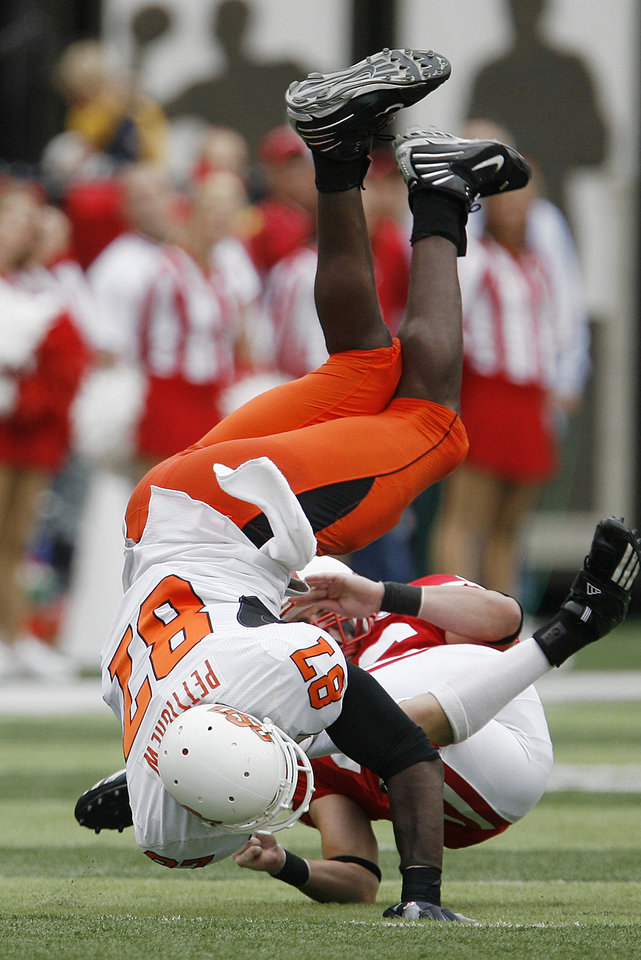 Photo - Brandon Pettigrew of OSU is flipped upside down by Ben Eisenhart of Nebraska during  the college football game between Oklahoma State University (OSU) and the University of Nebraska at Memorial Stadium in Lincoln, Neb., on Saturday, Oct. 13, 2007. By Bryan Terry, The Oklahoman