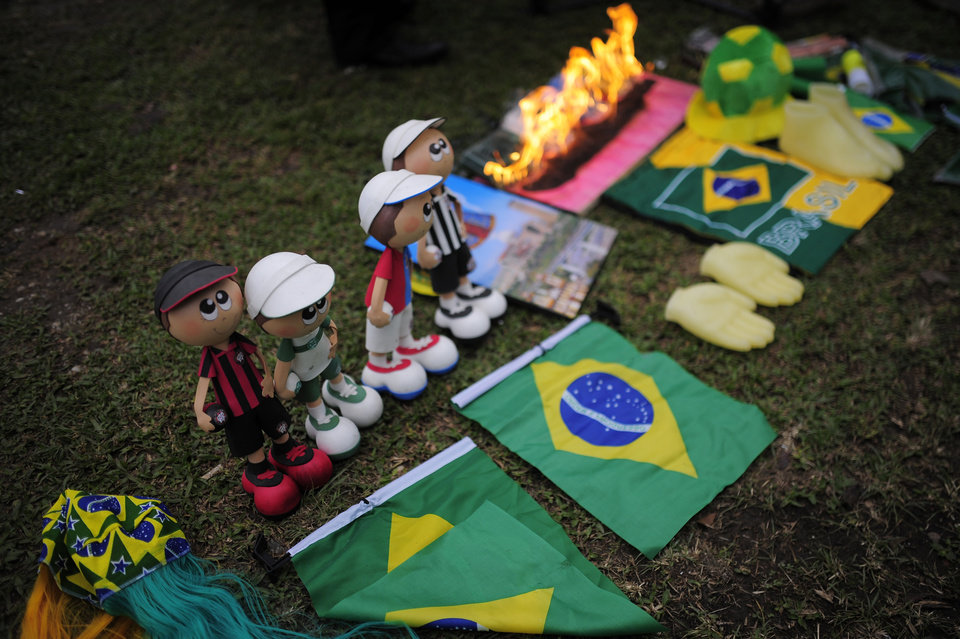 Photo - Materials belonging to witchdoctor Chik Jeitoso are displayed on a patch of grass outside the Arena da Baixada stadium in Curitiba, Brazil, Wednesday, June 11, 2014. During the performance Jeitoso, a famous witchdoctor from Curitiba, predicted difficulties for Brazil in the World Cup and that the bad energies are likely to affect Neymar and Messi during the competition. (AP Photo/Manu Fernandez)