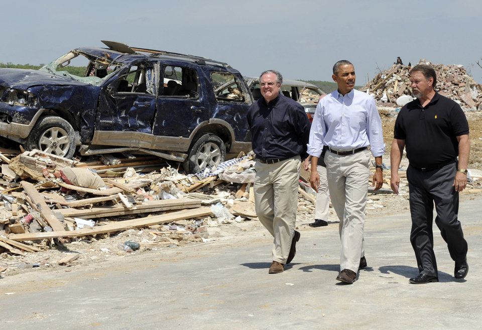 Photo - President Barack Obama tours tornado-damaged areas of Vilonia, Ark., Wednesday, May 7, 2014 and walks with Sen. Mark Pryor, D-Ark., left. Obama is visiting with first responders and families affected by the recent tornados before traveling on to California where he will raise money for the Democratic Party and receive an award from a foundation created by movie director Steven Spielberg. (AP Photo/Susan Walsh)