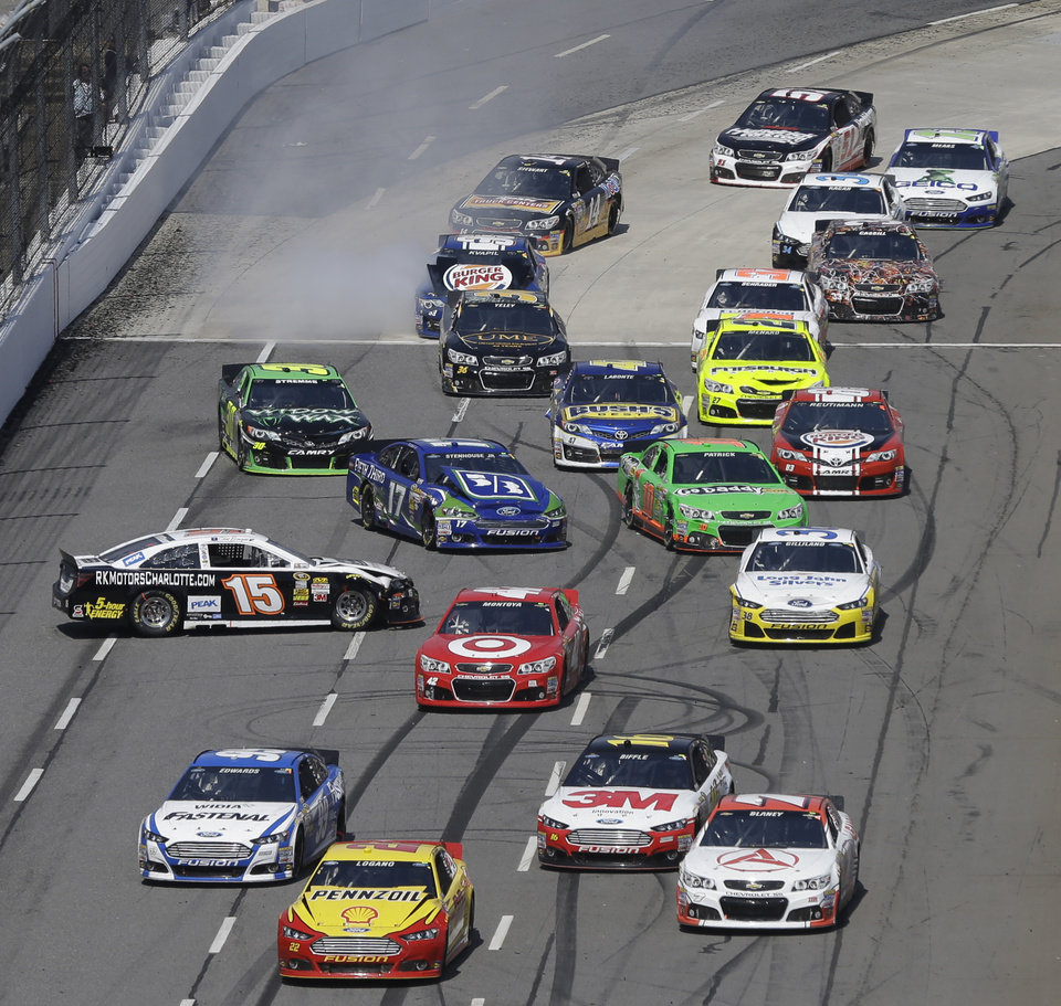 Clint Bowyer (15) spins out on the front stretch as the field passes during the STP 500 NASCAR Sprint Cup series auto race at Martinsville Speedway in Martinsville, Va., Sunday, April 7, 2013.  (AP Photo/Steve Helber)