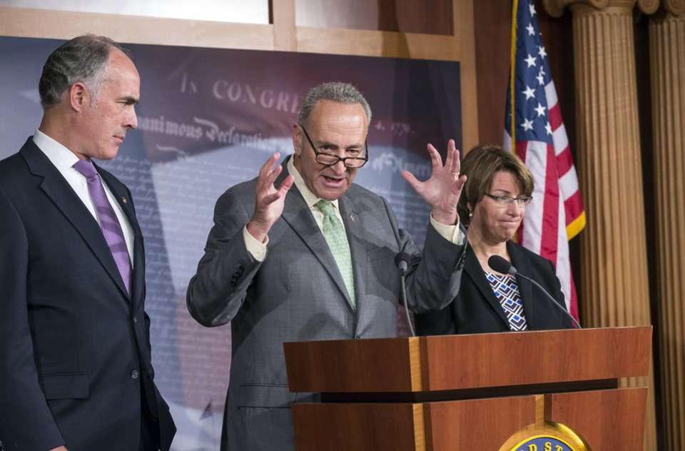 Photo - Sen. Chuck Schumer, D-N.Y., chairman of the Rules Committee, center, flanked by Sen. Robert Casey, D-Pa., left, chairman of the Subcommittee on Fiscal Responsibility and Economic Growth, and Sen. Amy Klobuchar, D-Minn., right, Senate chair of The Joint Economic Committee, speaks to reporters about the economic consequences of a debt ceiling default, during a news conference at the Capitol, Wednesday, Sept. 18, 2013. House GOP leaders Wednesday announced that they will move quickly to raise the government's borrowing cap by attaching a wish list of GOP priorities like blocking Obamacare, forcing construction of the Keystone XL pipeline and setting the stage for reforming the loophole-cluttered tax code. (AP Photo/J. Scott Applewhite)