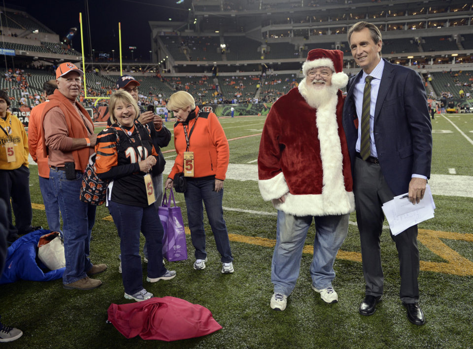 Photo -   FILE - This Oct. 21, 2012 file photo shows former Cincinnati Bengals receiver and current television personality Cris Collinsworth talking with fans prior to an NFL football game against the Pittsburgh Steelers in Cincinnati. Collinsworth figures his announcing career benefited from the fact he wasn't a household name as an NFL player. He learned from his mistakes calling games watched by small numbers of fans, slowly working his way up to his current high-profile gig on
