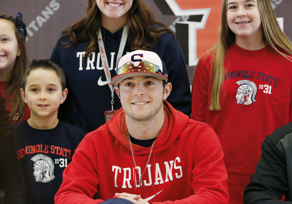 Photo - With his siblings standing near him, Carter LaValley, poses for a picture after the senior signed a letter to play at Seminole State College during Signing Day ceremony at Carl Albert  High School on Wednesday, Feb. 6, 2019.  Photo by Jim Beckel, The Oklahoman.