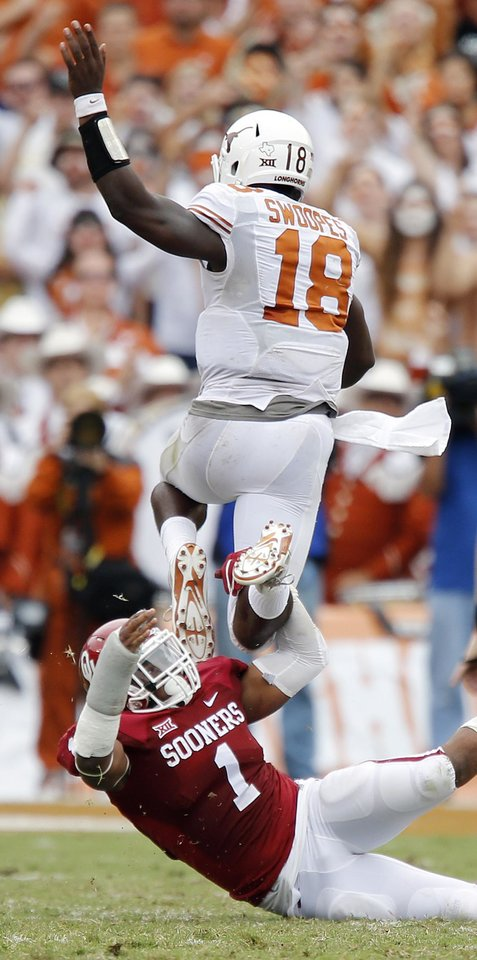 Photo - Texas' Tyrone Swoopes (18) leaps over Oklahoma's Dominique Alexander (1) during the college football game between the University of Oklahoma Sooners (OU) and the University of Texas Longhorns (UT) during the Red River Showdown at the Cotton bowl in Dallas, Texas on Saturday, Oct. 11, 2014. Photo by Chris Landsberger, The Oklahoman