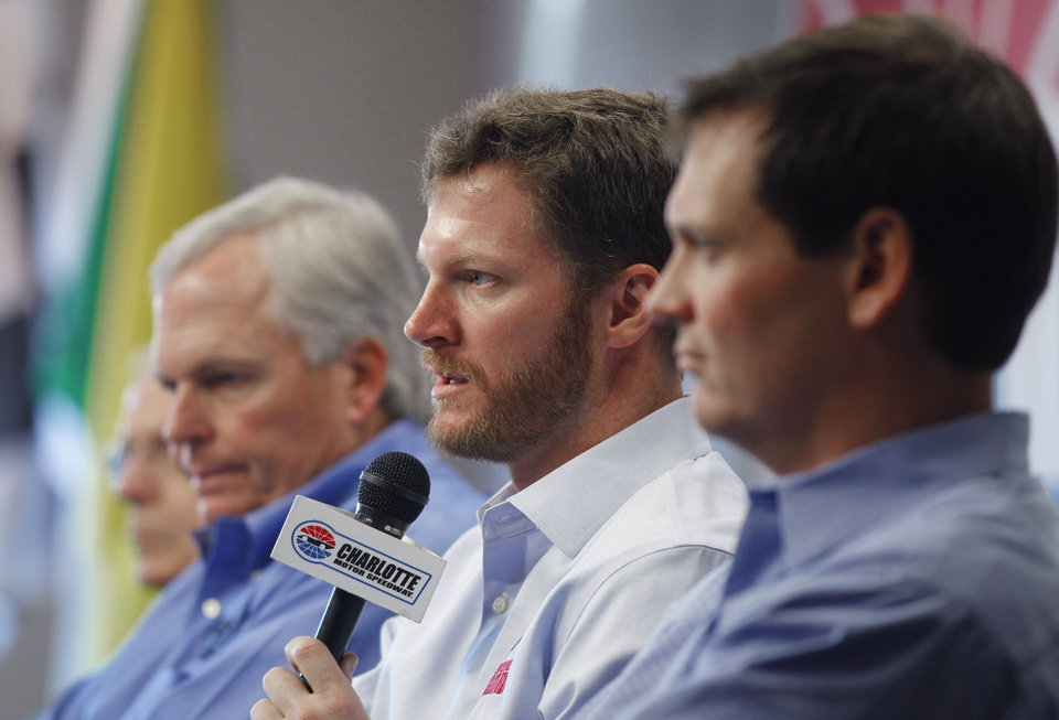 Photo -   Dale Earnhardt Jr, center, talks about missing the next two races with his second concussion in the past six weeks as team owner Rick Hendrick, left, and crew chief Steve Letarte, right, look on during a news conference prior to practice for Saturday's NASCAR Bank of America 500 NASCAR Sprint Cup series auto race in Concord, N.C., Thursday, Oct. 11, 2012. (AP Photo/Chuck Burton)