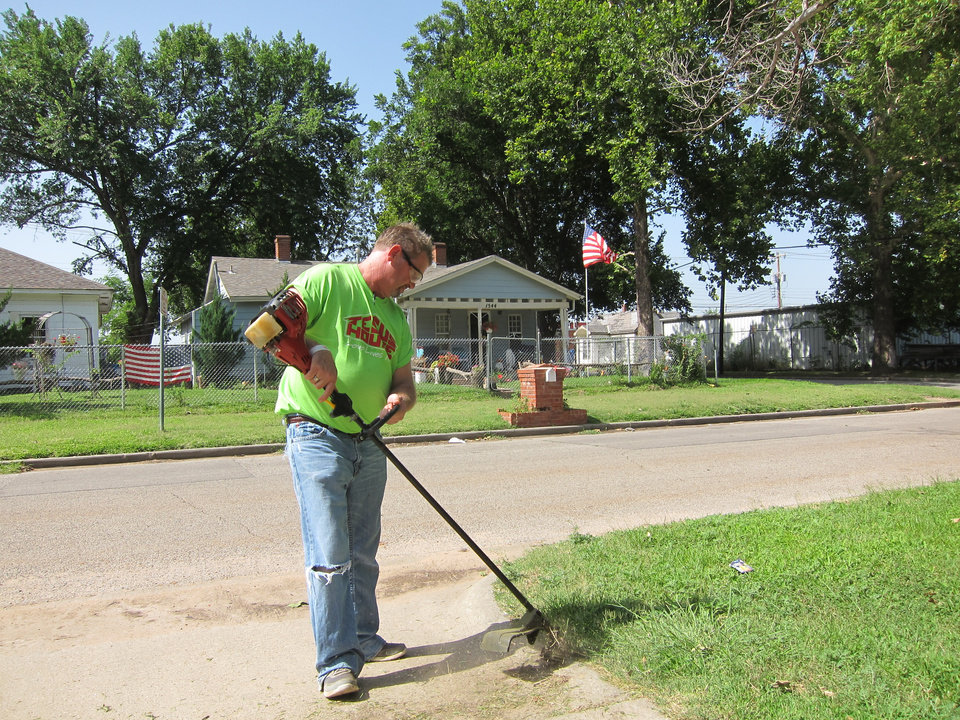 Photo -  Jesus House resident Richard Williams, 42, uses a weed eater on a lawn in the Orchard Park neighborhood during a recent Adopt-A-Block outing. Photo by Carla Hinton, The Oklahoman