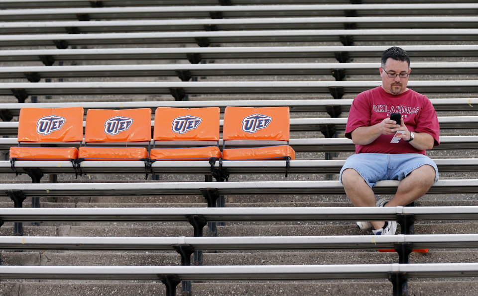Photo - Sooner fan Patrick Macmillan sits in the stands during the college football game between the University of Oklahoma Sooners (OU) and the University of Texas El Paso Miners (UTEP) at Sun Bowl Stadium on Saturday, Sept. 1, 2012, in El Paso, Tex.  Photo by Chris Landsberger, The Oklahoman