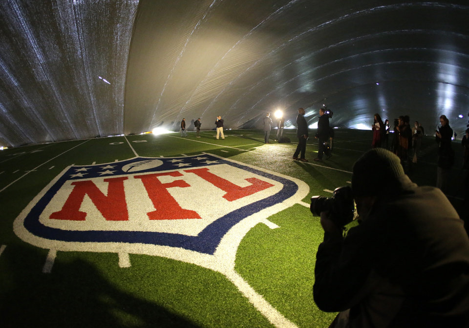 Photo - FILE - In this Jan. 15, 2014 file photo, the NFL logo at midfield of MetLife Stadium is illuminated by lights on television reporters' videocameras as members of the media are given a tour under a tarp used by crews to keep the turf dry ahead of Super Bowl XLVIII in East Rutherford, N.J. As the Denver Broncos and Seattle Seahawks prep for their Feb. 2, 2014 showdown in the Super Bowl, a legal fight is playing out over the very turf installed months ago at the NFL title game's venue. Taylor Turf Installation Inc. is suing the MetLife Stadium's operators and the company that hired the suburban St. Louis company, seeking more than $292,000 that Taylor Turf claims it still is owed for hustling to install the  stadium's playing surface last summer. (AP Photo/Julio Cortez, File)
