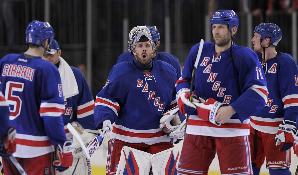 Photo -   New York Rangers goalie Henrik Lundqvist, center, of Sweden, reacts as he celebrates with teammates after defeating the Ottawa Senators 2-1 in Game 7 of a first-round NHL hockey Stanley Cup playoff series on Thursday, April 26, 2012, in New York. (AP Photo/Julio Cortez)