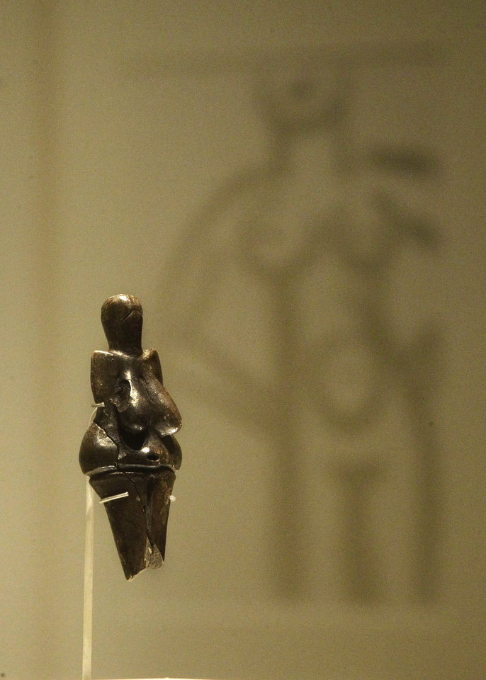 Backdropped by a reflection of Henri Matisse\'s 1950 painting \'Grand nu\', a sculpture of nude created in baked clay dates from between 31,000 and 27,000 years ago, discovered at Dolni Vestonice, Moravia, Czech Republic is seen on display in an exhibition \'Ice Age Art : arrival of the modern mind\' at the British Museum in London, Tuesday, Feb. 5, 2013. The sculpture The exhibition present masterpieces create from the last Ice Age between 40,000 and 10,000 years ago, drawn from across Europe, by artists with modern minds and presented alongside modern works to illustrate the fundamental human desire to communicate and make art as a way of understanding ourselves and our place in the world. (AP Photo/Sang Tan)