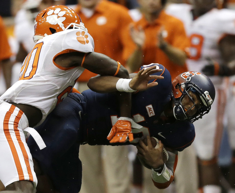Syracuse quarterback Terrell Hunt, right, is tackled by Clemson safety Jayron Kearse (20) during the second half of an NCAA college football game on Saturday, Oct. 5, 2013, in Syracuse, N.Y. Clemson won, 49-14. (AP Photo/Mike Groll)