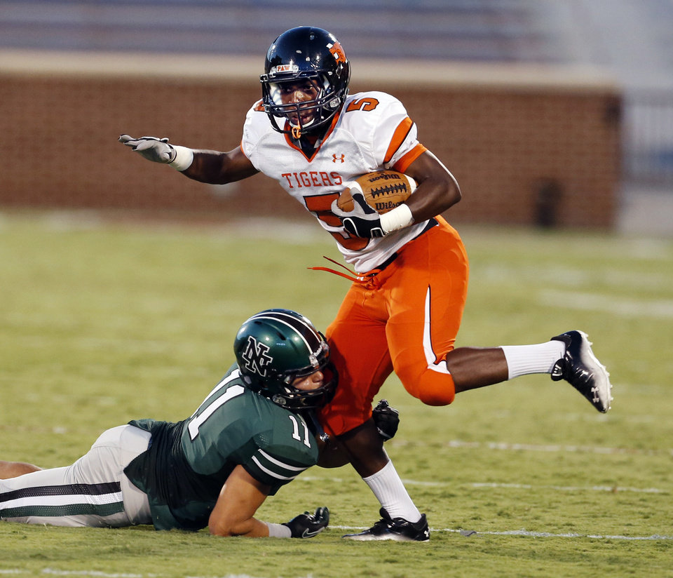 Photo - Norman High School Tiger Dupree Young (5) tries to escape from DJ Gasso (11) as they play high school football against the Norman North Timberwolves at Gaylord Family/Oklahoma Memorial Stadium on Thursday, Aug. 30, 2012 in Norman, Okla.  Photo by Steve Sisney, The Oklahoman